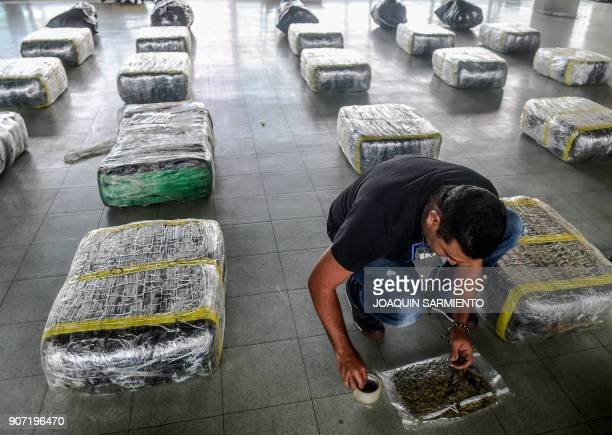 A member of the Colombian Technical Investigation Unit seals a package of seized marijuana on January 19 in Medellin Colombia 11 tons of marijuana...