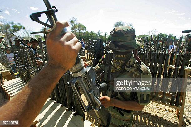 A member of the Colombian United Self Defense rightwing paramilitary guerrillas hands over his weapon during the demobilization ceremony 10 March...