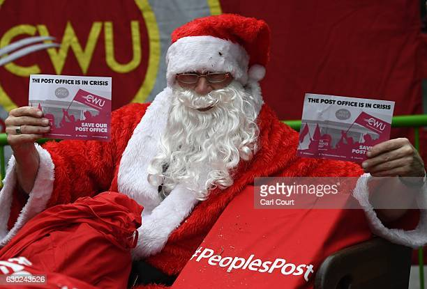 A member of the Communication Workers Union dressed in a Santa Claus costume takes part in a protest outside the Department for Business during...