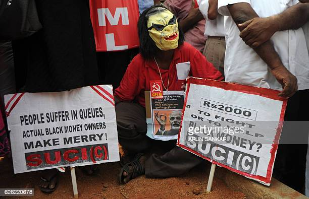 TOPSHOT A member of the Communist Party of India wears a mask as he holds placards during a protest against Indian Prime Minister Narendra Modi and...