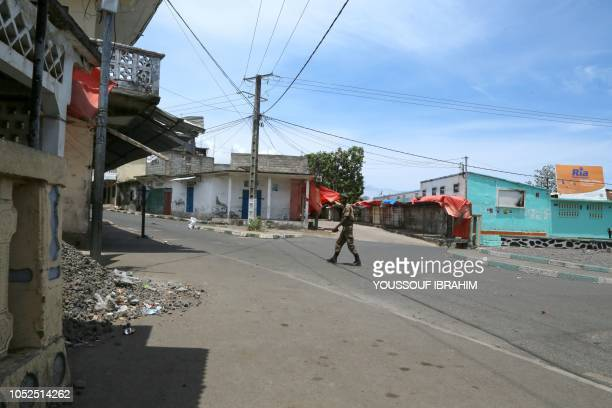 A member of the Comoros armed forces walks by the entrance of the Medina in Mutsamudu on the island of Anjouan Comoros on October 19 2018 Comoros...