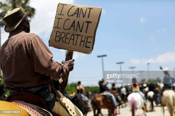 Member of the Compton Cowboys holds a sign reading 'I Can't I Can't Breathe' at a 'peace ride' for George Floyd on June 7, 2020 in Compton,...