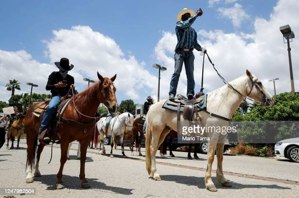 Member of the Compton Cowboys takes a photo at a 'peace ride' for George Floyd on June 7, 2020 in Compton, California. This is the 13th day of...