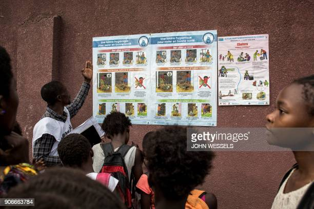 TOPSHOT A member of the Congolese Red Cross explains the symptoms risks and precautions of cholera to children in Kinshasa on January 18 2018 The...