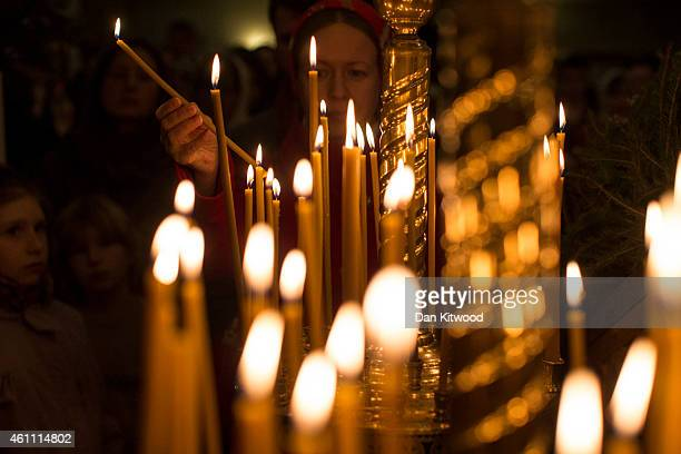 A member of the congregartion lights a candle during a midnight mass vigil at the Russian Orthodox Church Abroad's 'Cathedral of the Dormition of the...