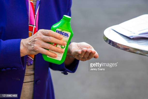 A member of the congregation applies hand sanitiser before the commencement of a service held in the yard of St Paul's Anglican Church in Burwood...