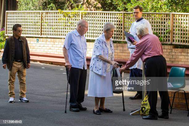 A member of the congregation lines up for hand sanitiser before the commencement of a service held in the yard of St Paul's Anglican Church in...