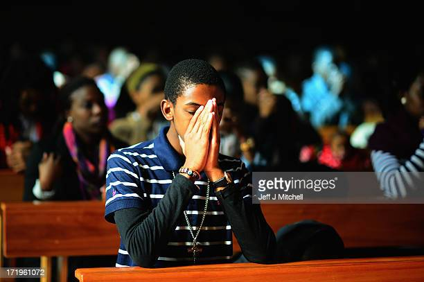 A member of the congregation prays during Sunday service at Regina Mundi Church in Soweto on June 30 2013 in Johannesburg South Africa People...