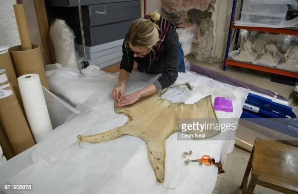 A member of the conservation team finishes cleaning the material before the fitting of a 'pair of straight bodies' to the funeral effigy of Elizabeth...