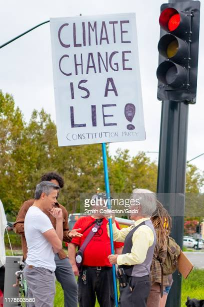 Member of the Constitution party holds a sign reading Climate Change is a Lie during a counter protest responding to climate change protests in San...