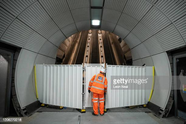 A member of the construction team looks through a gap in a barrier at the base of the escalator system in Liverpool Street Crossrail station on...