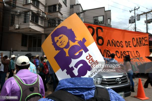 A member of the Council of Popular and Indigenous Organizations of Honduras carries a poster with an image of slain indigenous leader and...