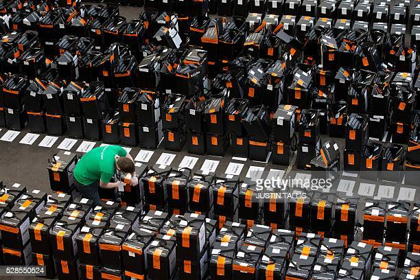 A member of the count staff cuts the seal on an unprocessed ballot box awaiting processing at a count centre in north London on May 6 2016 Early...