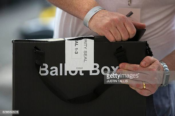 A member of the count staff opens a sealed ballot boxes containing voting slips as they are prepared for counting at a count centre in north London...