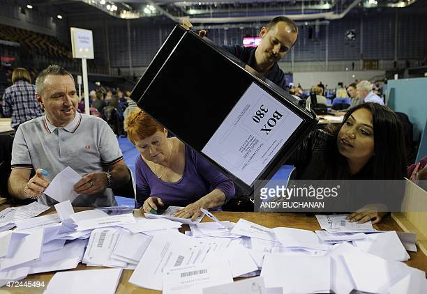 A member of the counting staff reaches into a ballot box to extract the last of the papers at the counting centre at the Emirates Arena in Glasgow on...