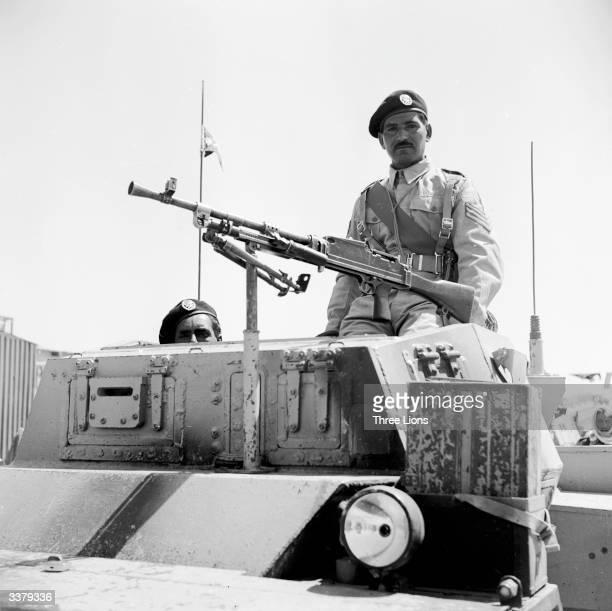 Member of the crack Jordanese regiment the Arab Legion, sitting behind a machine gun fixed to an armoured car.
