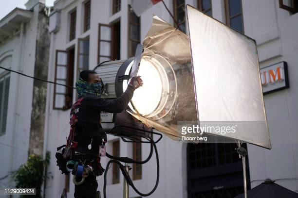 A member of the crew handles lighting equipment during the production of the film Sin in Jakarta Indonesia on Thursday Feb 14 2019 Hollywood studios...