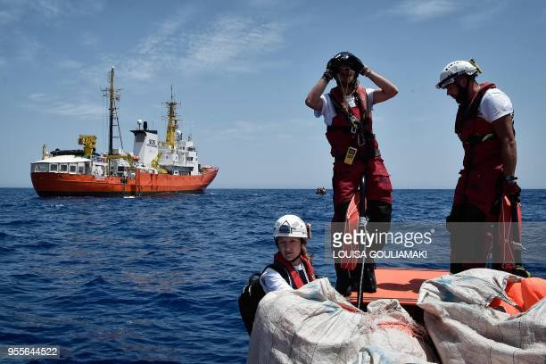 A member of the crew of MV Aquarius a rescue vessel chartered by SOSMediterranee and Doctors Without Borders watches a Libyan Coast Guard vessel...