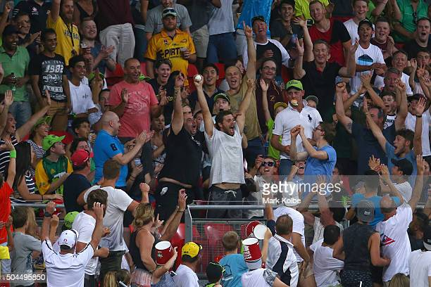A member of the crowd celebrates after catching a six during the Big Bash League match between the Sydney Thunder and the Melbourne Renegades at...