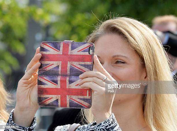 A member of the crowd takes a photograph on their mobile phone of Queen Elizabeth II during a walkabout on Pariser Platz close to the Brandenburg...