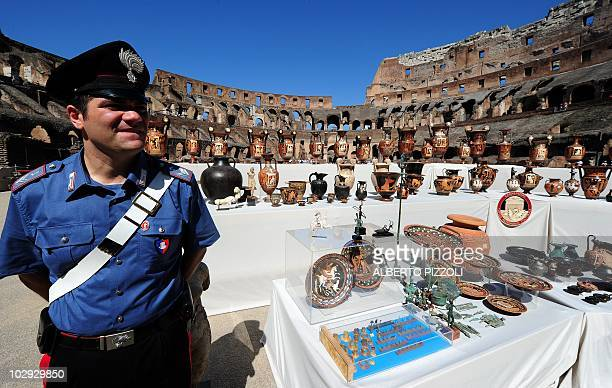 A member of the cultural heritage unit of the Italian Carabinieri stands on July 16 2010 at Rome's Colosseum next to 337 archaeological artefacts...
