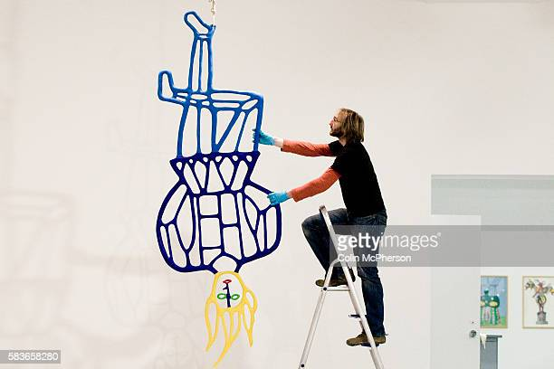 A member of the curating staff at the Tate gallery in Liverpool adjusts a piece of work by French artist Niki de Saint Phalle prior to the opening of...