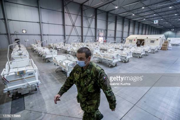 Member of the Czech Army walks past medical beds inside of field hospital built in an exhibition center for patients who suffer the coronavirus...