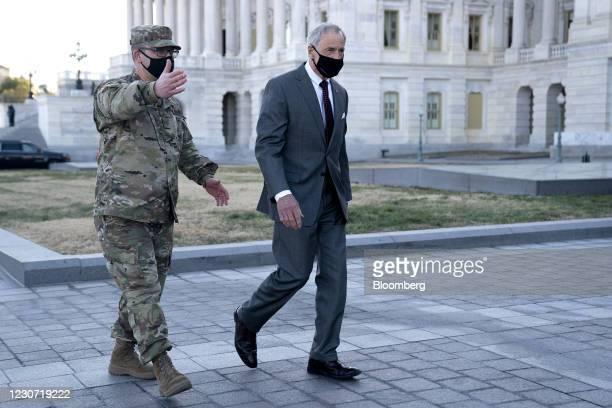 Member of the Delaware National Guard speaks to Senator Tom Carper, a Democrat of Delaware, outside the U.S. Capitol in Washington, D.C., U.S., on...