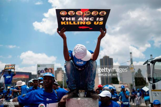 TOPSHOT A member of the Democratic Alliance sits on a barricade as he holds a sign reading the ANC is killing us in reference to South African ruling...