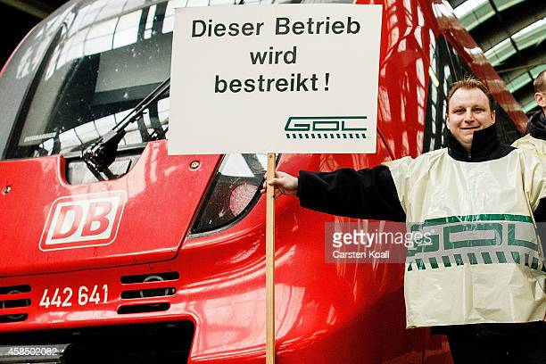 A member of the Deutsche Lokfuehrer GewerkschaftGDL holds a placard with the slogan This establishment is on strike in front of a train of the...