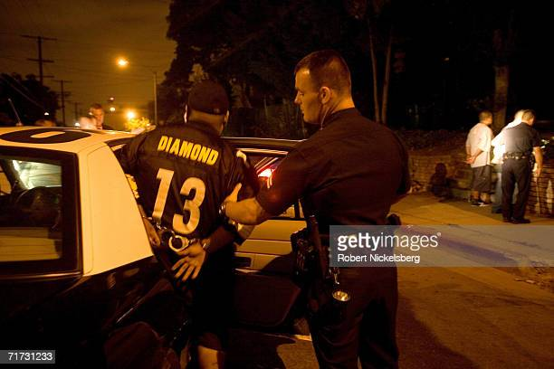 A member of the Diamond Street hispanic street gang is helped into a Los Angeles Police Department gang unit car following his arrest for drug...