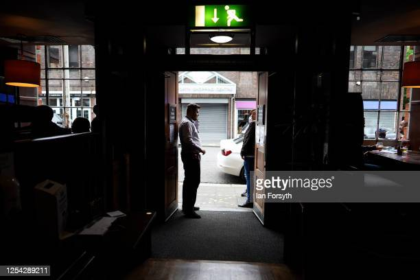 Member of the door staff briefs customers on the new measures adopted on the first day of pubs reopening at the Job Bulman pub in Gosforth on July...