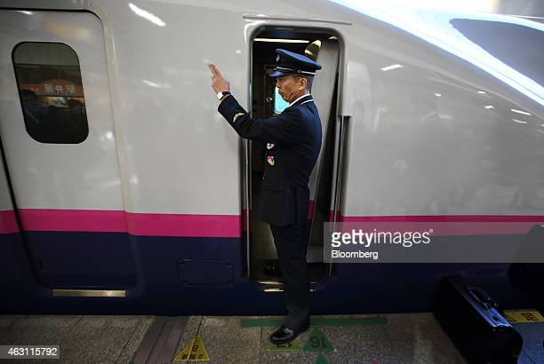 A member of the East Japan Railway Co train crew gestures as an E3 series Shinkansen bullet train prepares to depart from Sendai Station in Sendai...
