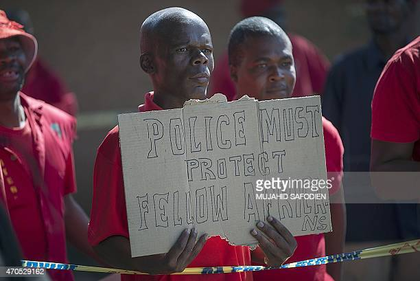 A member of the Economic Freedom Fighters holds a placard as he stands outside the Wynberg Magistrate court in Alexandra Township Johannesburg on...