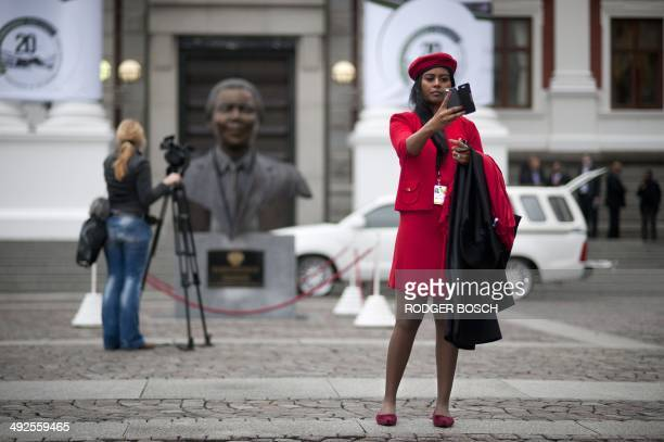 Member of the Economic Freedom Fighters take a photo of herself in front of the South African parliament before for the first session of the newly...