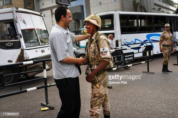 A member of the Egyptian military is greeted in support by a pedestrian in the district of Giza the morning after the first democratically elected...