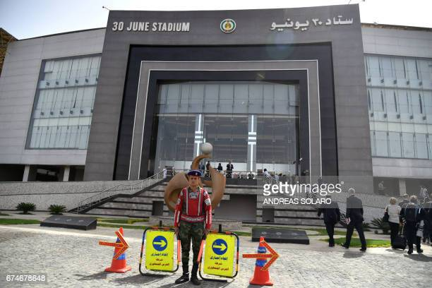 A member of the Egyptian Republican Guard keeps watch as people walk outside the stadium where Pope Francis will lead mass on April 29 2017 in Cairo...