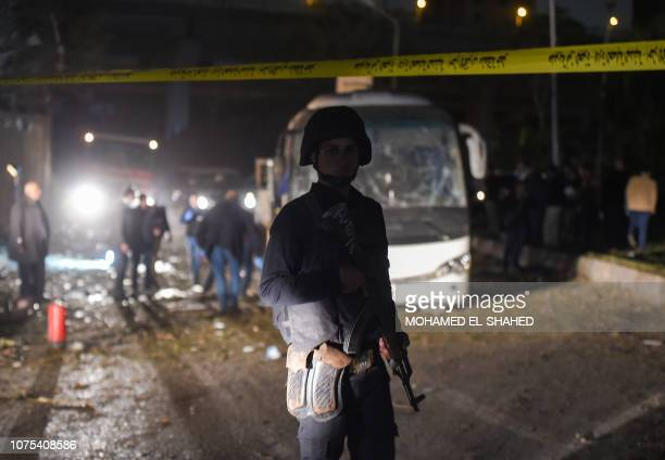 A member of the Egyptian security forces stands guard at the scene of an attack on a tourist bus in Giza province south of the Egyptian capital Cairo...