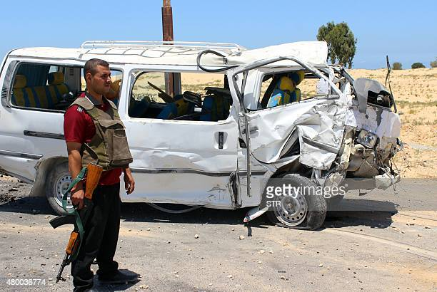 A member of the Egyptian security forces stands guard next to a damaged bus following a roadside bomb blast which wounded 20 Egyptian policemen on...