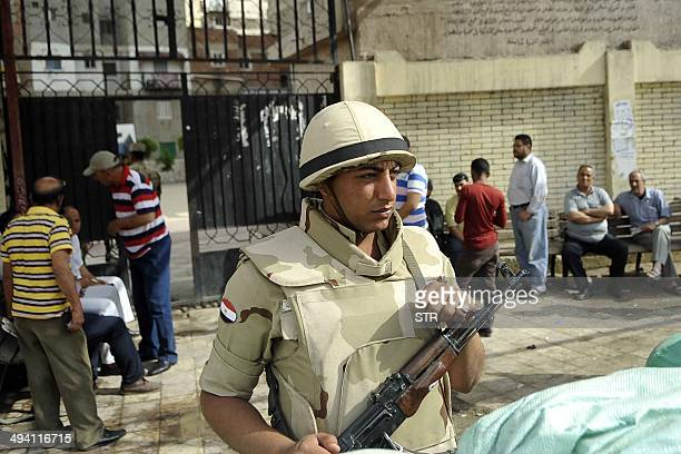 A member of the Egyptian security forces stands guard outside a polling station as Egyptian wait to cast their vote in Egypt's northern coastal city...