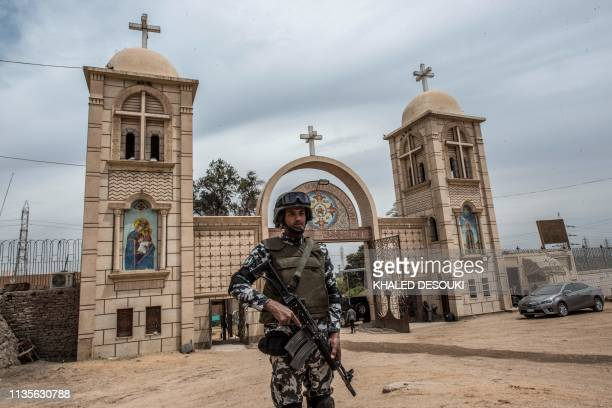 """Member of the Egyptian security forces stands guard outside the gatehouse of the Coptic Orthodox """"White Monastery"""" of St Shenouda the Archimandrite..."""