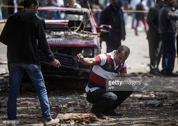 A member of the Egyptian security personnel inspects the scene after twin bombs struck police posts near Cairo University in the centre of Egypt's...