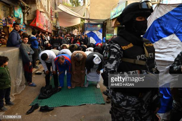 A member of the Egyptian special forces stands guard as people pray outside a mosque during the funeral of policeman Mahmud Abu elYzied one of three...