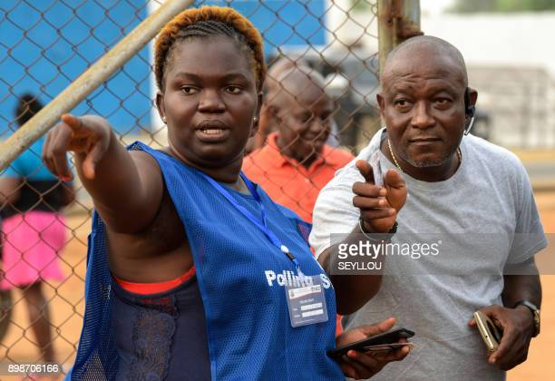 A member of the electoral commission gestures as Liberians go to the polls in Monrovia for the second round of presidential elections on December 26...