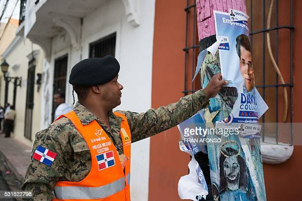 A member of the electoral military police removes a campaign poster from a polling station during general elections in Santo Domingo on May 15 2016...