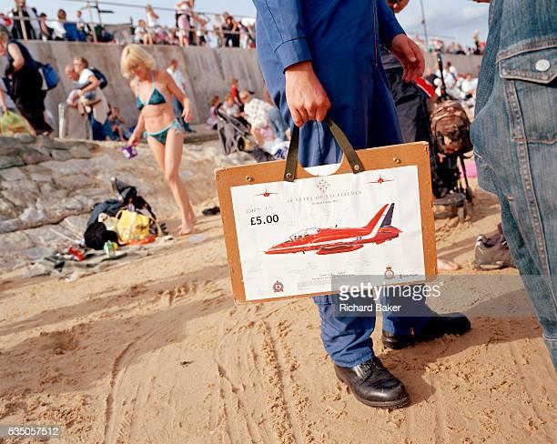 A member of the elite 'Red Arrows' Britain's prestigious Royal Air Force aerobatic team sells RollsRoycesponsored charity posters of their workhorse...