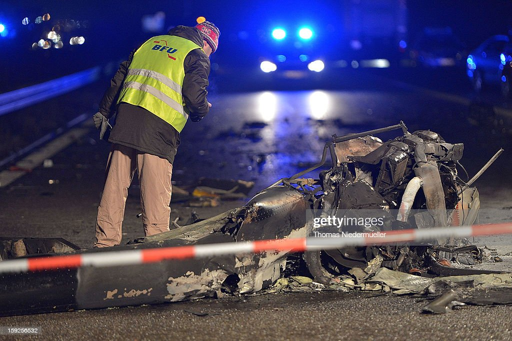 A member of the emergency services surveys the wreckage of a helicopter that crashed onto the A6 highway on January 10, 2013 near Schwabisch Hall, Germany. According to police the helicopter struck a nearby power line and exploded, killing the pilot and leaving one vehicle driver with minor injuries.