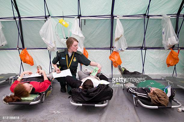 A member of the emergency services treats a 'casualty' played by actors in a triage centre during the Exercise Unified Response planned training...