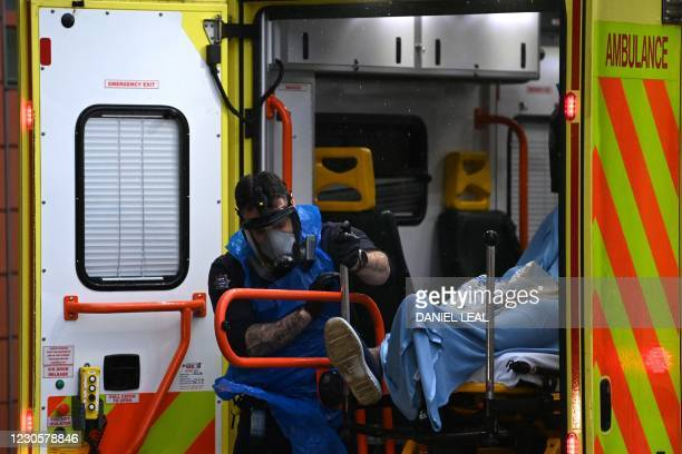 Member of the emergency services unloads a patient from an ambulance at the Royal London hospital in east London on January 14, 2021.