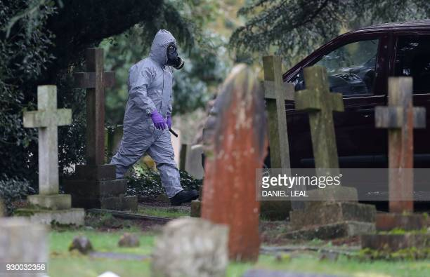 TOPSHOT A member of the emergency services wearing a protective suit works at the London Road Cemetery in Salisbury southern England on March 10...